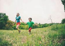 A woman and her son are running along the grass. A women and her son are running along the green grass. Mom holds the child by the hand and laughs. A boy is Stock Photo