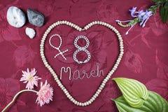 Women& heureux x27 ; carte de voeux de jour de s La pierre laisse des fleurs et des graines Photos stock