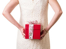 Women hiding a Christmas gift. A woman in a white lacy party dress holding a Christmas present behind her back Stock Images