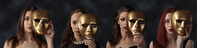 Women hiding faces behind golden masks Stock Photos