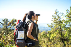 Women hiker with backpack checks map to find directions and look binoculars in wilderness area at mountain and forest. Royalty Free Stock Images