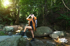 Women hiker with backpack checks map to find directions and look binoculars in wilderness area at waterfalls and forest. Travel Concept Stock Photos