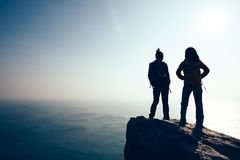 Women hikers looking at the view on seaside mountain top rock edge. Two women hikers looking at the view on seaside mountain top rock edge Royalty Free Stock Image