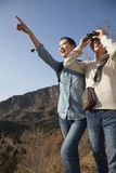 Women hiking, using binoculars, pointing at the mountain top Stock Photos