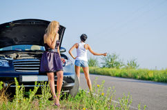 Women hitchhiking after a breakdown. With their car pulled to the side of a country road with the hood up Royalty Free Stock Photo