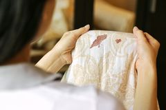 Women hold bed sheet with period blood spot stains on blur background. Need to be cleaning.  Stock Images
