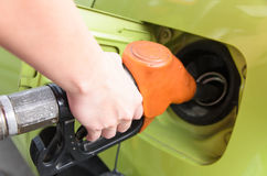 Women hold Fuel nozzle to add fuel in car at gas station Stock Photos