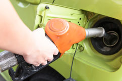 Women hold Fuel nozzle to add fuel in car at gas station Stock Photo