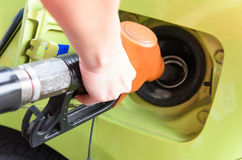 Women hold Fuel nozzle to add fuel in car at gas station Stock Images
