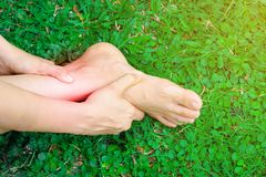 Women hold her sprained ankle caused by an accident. Injured person feeling pain and using hand hold on painful sprained to reduce royalty free stock photography