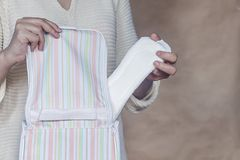 Women hold a menstrual pad. Young woman taking out a sanitary pad from her bag. White menstrual pad royalty free stock image