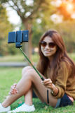 Women hold monopod use smart phone take photograph selfie in park royalty free stock images