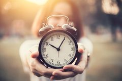 Women hold vintage clock in her hand for showing times. To do concept stock photos