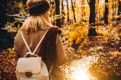 Women holding bouquet of autumn leaves in front of beautiful colorful landscape with a stream and forest in autumn Royalty Free Stock Photos