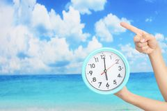 Women holding a clock. At the beach stock image