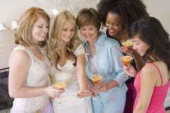 Women Holding Cocktail Glass And Looking At Engagement Ring. Happy women holding cocktail glass and looking at engagement ring at hen party Royalty Free Stock Photos