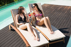 Women holding drinks by swimming pool Royalty Free Stock Photography