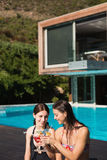 Women holding drinks by swimming pool Stock Images