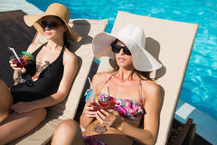 Women holding drinks by swimming pool Stock Image