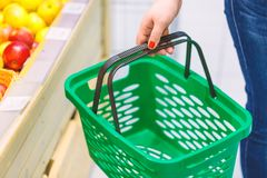 Women holding empty green shopping basket near fruits window in the supermarket. Shopping concept.  Stock Photography