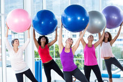Women holding exercise balls with arms raised Royalty Free Stock Photos