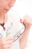Women holding eye glasses Royalty Free Stock Images