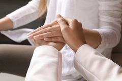 Women holding hands indoors, closeup. Concept of support and help royalty free stock image