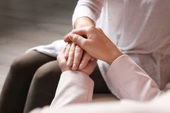 Women holding hands indoors, closeup. Concept of support and help stock photo