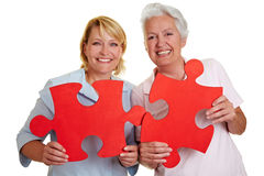 Women holding jigsaw puzzle pieces. Two happy senior women holding jigsaw puzzle pieces Stock Photography