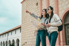 Women holding map and pointing to somewhere stock photography