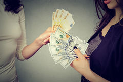 Women holding money exchanging with each other dollars to euro cash royalty free stock image