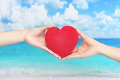 A red heart love symbol. Women holding a red heart love symbol stock image