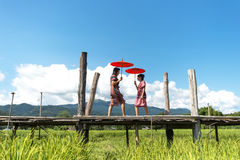 The Women holding a red umbrella and walk on the wooden bridge in the green rice field. Mae Hongson Thailand. Royalty Free Stock Photography