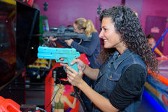 Women holding rifle arcade game. Women holding rifle of arcade game Stock Photos