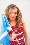 Women holding Scottish flag. Attractive young woman in colorful dress holding the blue and white  Scottish flag , the Saltire, on a bright  background Royalty Free Stock Images
