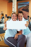 Women holding sign in gym Royalty Free Stock Image
