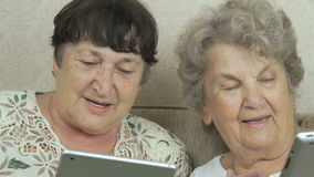 Women holding the silver digital tablets. Women sitting on a beige sofa at home. Each woman holds the silver digital tablet stock video footage