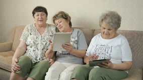 Women holding the silver digital tablets. Women sitting on a beige sofa at home. Two women hold the silver digital tablet stock video footage