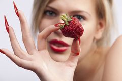 Women holding single strawberry Royalty Free Stock Photo