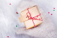 Women is holding a small gift box in hands worn in white knitted mittens Royalty Free Stock Photo