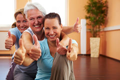 Women holding thumbs up in gym Stock Photos