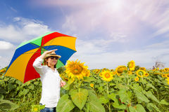 A women holding umbrella with field blooming of sunflowers. Royalty Free Stock Images