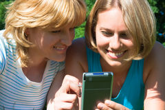 Women holds the pocket computer. Two women with a handheld Royalty Free Stock Image