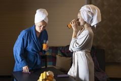 Women in home clothes drink juice. Women in home clothes drink juice from glasses. Women are dressed in dressing gowns. On his head to tie a towel stock image