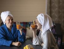 Women in home clothes drink juice. Women in home clothes drink juice from glasses. Women are dressed in dressing gowns. On his head to tie a towel stock photo