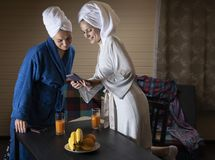 Women in home clothes drink juice. Women in home clothes drink juice from glasses. Women are dressed in dressing gowns. On his head to tie a towel stock photography