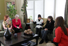 Women at home meeting. Four women listen on as another enthusiastically shares her ideas at a home meeting Stock Images