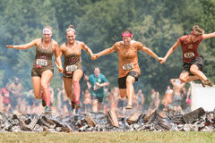 Women Hurdle Burning Logs Together In Extreme Obstacle Course Race Stock Photos