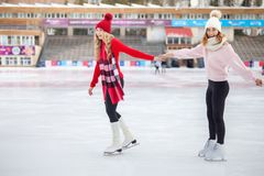 Women ice skating outdoor at ice rink stock photo