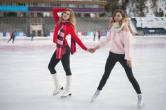 Women ice skating outdoor at ice rink royalty free stock image